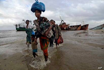 A displaced family arrives after being rescued by a boat from a flooded area of Buzi district, 200 kilometers (120 miles) outside Beira, Mozambique, on March 23, 2019.