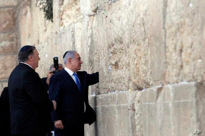 Israeli Prime Minister Benjamin Netanyahu accompanied by U.S. Secretary of State Mike Pompeo touches the stones of the Western Wall during Pompeo's visit to the site in Jerusalem's Old City, March 21, 2019.
