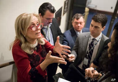 Rep. Debbie Dingell, D-Mich. (L) responds to reporters after members of the House Democratic Caucus met on Capitol Hill in the wake of reports of sexual misconduct by Rep. John Conyers, D-Mich., the longest-serving member of the House, in Washington,...