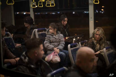 Noor, 8 (C) sits with her sister Maryam, 18, and their mother Nadia Hanan Madalo, 46 (R) as they wait in an airport bus in Irbil, Iraq, March 15, 2017. An Iraqi family has landed in the United States as a federal court blocked a travel ban that would...