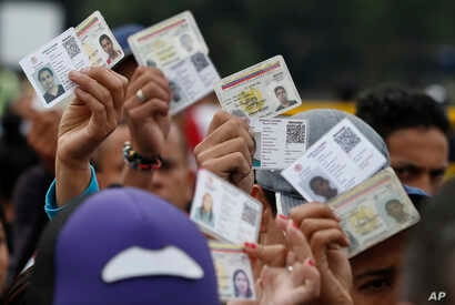 Venezuelan citizens hold up their identification cards for inspection by the Colombian immigration police, in Cucuta, Colombia, on the border with Venezuela, Feb. 22, 2018.