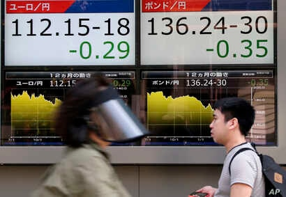 People walk by an electronic board displays exchange rate of euro, left, and British pound at the securities firm in Tokyo, Monday, June 27, 2016.