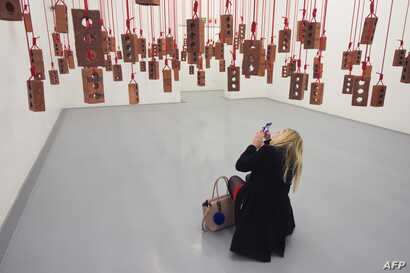 A visitor takes photos of an artwork by South African artist Kendell Geers, during the media opening of the Zeitz Museum of Contemporary Art Africa on Sept. 15, 2017 in Cape Town.