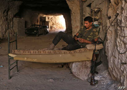 A Syrian rebel fighter rests at an unknown location in  Idlib province, Sept. 5, 2018.