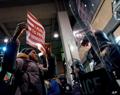 A protester stands facing police officers at an entrance of Terminal 4 at John F. Kennedy International Airport in New York, Jan. 28, 2017, after earlier in the day two Iraqi refugees were detained while trying to enter the country.