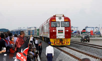 FILE - Kenyan President Uhuru Kenyatta (3rd-L) watches the opening of the SGR cargo train as it leaves the port containers depot in Mombasa to Nairobi, May 30, 2017. The project, a $3.3 billion investment backed by China, is the country's largest inf...