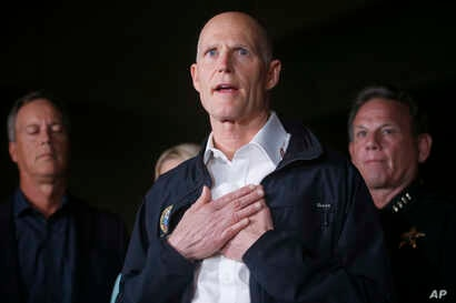 Florida Gov. Rick Scott gestures as he speaks during a news conference near Marjory Stoneman Douglas High School in Parkland, Fla., where a former student is suspected of killing at least 17 people, Feb. 14, 2018.