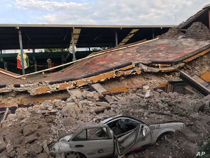 A car sits crushed, engulfed in a pile of rubble from a building felled by a 7.1 earthquake, in Jojutla, Morelos state, Mexico, Sept. 19, 2017.