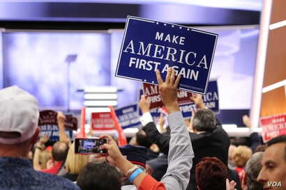 """A covention delegate holds a """"Make America First Again"""" sign at the Republican National Convention, July 20, 2016. (A. Shaker/VOA)"""