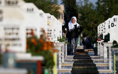 A woman stands in a cemetery during the funeral for a Syrian Democratic Forces fighter killed in Hajin during battles against the Islamic State group, in the Kurdish-controlled city of Qamishly in northeastern Syria, Dec. 3, 2018.