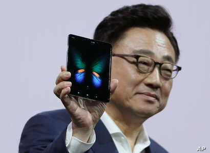 DJ Koh, president and CEO of IT and Mobile Communications, holds up the new Samsung Galaxy Fold smartphone during an event, Feb. 20, 2019, in San Francisco.
