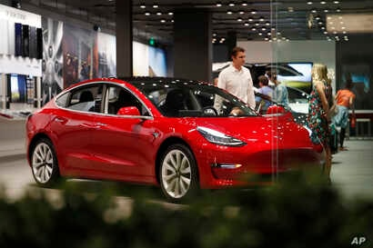 FILE- In this July 6, 2018, file photo, a prospective customer confer with sales associate as a Model 3 sits on display in a Tesla showroom in the Cherry Creek Mall in Denver.