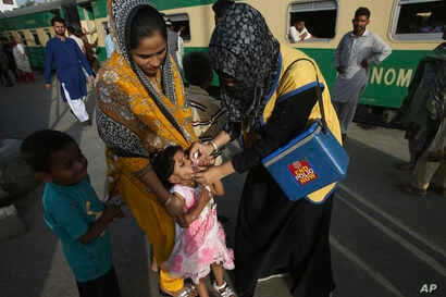A Pakistani health worker gives a polio vaccine to a girl at Karachi railway station in Pakistan, April 11, 2018.