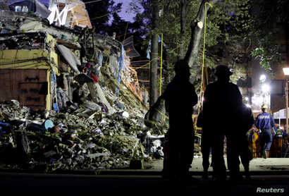 Rescue workers stand next to the rubble of a collapsed multi family residential, after an earthquake, in Mexico City, Mexico, Sept. 24, 2017.
