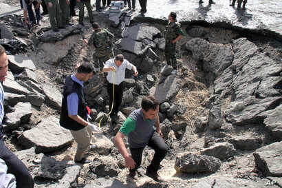 Syrian inspectors investigate the crater in front of a damaged military intelligence building where two bombs exploded in Damascus, Syria, May 10, 2012.