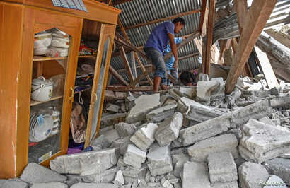 A villager walks through the ruins of a collapsed house during a search for the equipment of Malaysian tourists who died during the earthquake at the Sembalun Selong village in Lombok Timur, Indonesia, July 29, 2018.