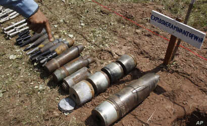 FILE - A Cambodian demining expert points to unexploded bombs displayed on the ground before a destruction ceremony organized by the Cambodia Mine Action Center (CMAC) at the complex of the Preah Vihear temple in Preah Vihear province, about 245 kilo...