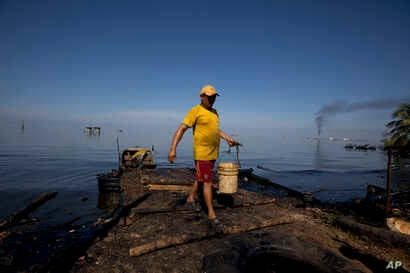 A fisherman collects water contaminated with oil from Maracaibo Lake in Cabimas, Venezuela, Aug. 20, 2018. The fisherman will use the water to clean fish. Broken down oil platforms span the vast lake, with downwind shores soaked in oil.