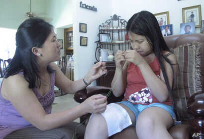 FILE - Vicky Xiong, left, teaches her daughter Rachel Lor how to do Hmong embroidery at their home in Fresno, Calif., April 22, 2012. Hmong refugees migrated in large numbers to California's Central Valley after fighting in America's secret war in La...
