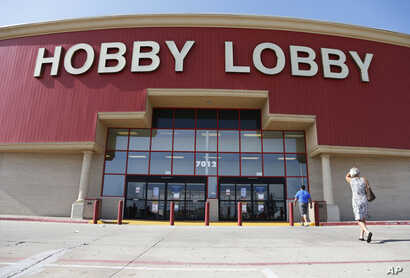 FILE - Customers walk to a Hobby Lobby store in Oklahoma City, June 30, 2014. A Hobby Lobby spokesman told The Associated Press Wednesday that a report that the company was considering going out of business is not true.