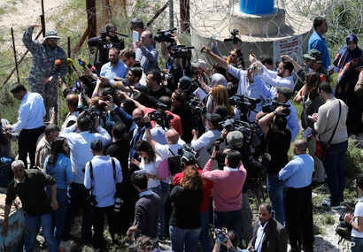 A Hezbollah officer, who identified himself as Ehab, top left, explains to journalists about the defensive measures established by the Israeli forces to prevent against any Hezbollah infiltration into Israel, at Labbouneh, south Lebanon, April 20, 20...