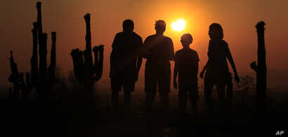 FILE - People view an annular solar eclipse as they look towards the setting sun on the horizon in Phoenix, Arizona, May 20, 2012.