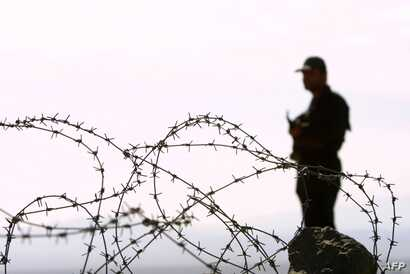 FILE - An Iranian guard stands on a mound at Mirjaveh point, where the borders of Iran, Afghanistan and Pakistan meet, Dec. 2, 2003.