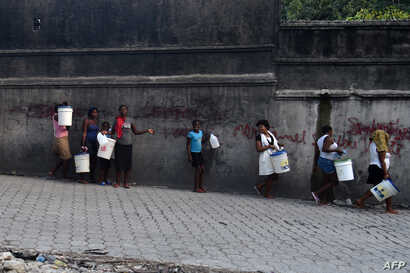 A group of women and children walk to buy water in the neighborhood of Petion Ville, in the Haitian Capital Port-au-Prince, on Feb. 14, 2019.