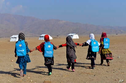 Afghan schoolgirls walk towards their tent classrooms on the outskirts of Jalalabad, capital of Nangarhar province, Afghanistan, Tuesday, Dec. 13, 2016.