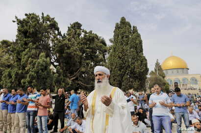 The Dome of the Rock is seen in the background as Palestinian men take part in Friday prayers on the compound known to Muslims as Noble Sanctuary and to Jews as Temple Mount in Jerusalem's Old City, Oct. 23, 2015.