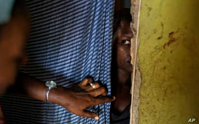 FILE - A 15-year-old girl who was raped when she was 14 talks to a member of UNICEF staff, left, at her home in a village near Masaka, Uganda, June 1, 2017.