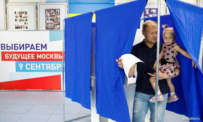 A man leaves a voting cabin at a polling station in Moscow, Sept. 9, 2018.
