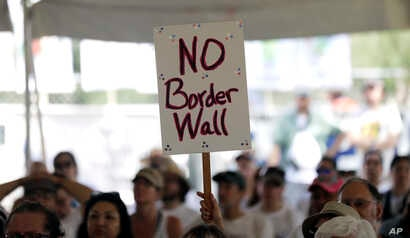 "FILE - A ""no border wall"" sign is held during a rally to oppose the wall the U.S. government wants to build on the river separating Texas and Mexico, Aug. 12, 2017, in Mission, Texas."