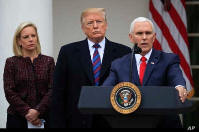 President Donald Trump joined by Homeland Security Secretary Kirstjen Nielsen, left, listens to Vice President Mike Pence speaks in the Rose Garden of the White House in Washington after a meeting with Congressional leaders on border security, Jan. 4...
