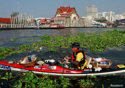 FILE - A volunteer rows his kayak as he collects trash in the Chao Praya river to raise public awareness on the damage single-use plastic has on the environment in Bangkok, Thailand, Dec. 21, 2018.