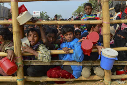 Rohingya refugees wait for food aid at Thankhali refugee camp in Bangladesh's Ukhia district on January 12, 2018.