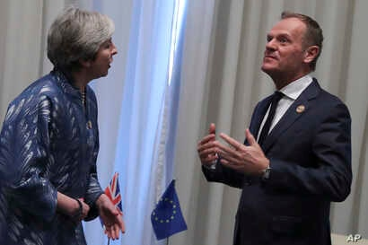FILE - European Union Council President Donald Tusk (R) speaks with British Prime Minister Theresa May during a bilateral meeting on the sidelines of a summit of EU and Arab leaders at the Sharm El Sheikh, Egypt, Feb. 24, 2019.