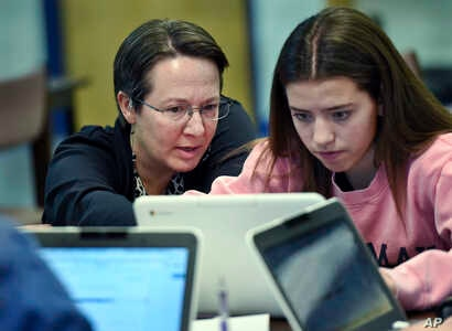 Jennifer Rocca, left, a teacher librarian at Brookfield, Conn., High School, works with Ariana Mamudi, 14, a freshman in her Digital Student class, Dec. 20, 2017. The required class teaches media literacy skills and has the students scrutinize source...