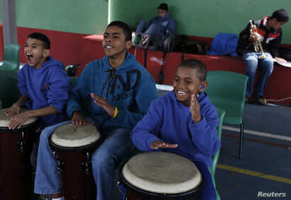 From left, students Joao Farias Alves, 11, Antonio Marques, 16, and Joao Pedro dos Santos Teixeira, 11, play bongos during their music class at the Madre Lucie Bray Municipal School for the Deaf in Sao Paulo, Sept. 4, 2012. The technique of teaching ...