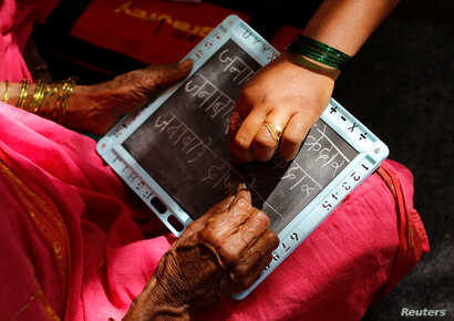 Sheetal Prakash More (R), a 30-year-old teacher, helps Janabai Kedar, 74,  as she writes on a slate at Aajibaichi Shaala (Grandmothers' School) in Fangane village, India, Feb. 15, 2017.