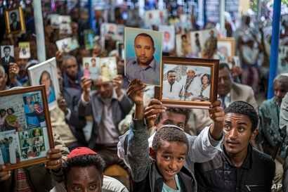 FILE - Members of Ethiopia's Jewish community hold up pictures of their relatives in Israel, during a solidarity event at a synagogue in Addis Ababa, Ethiopia, Feb. 28, 2018.