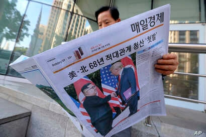 FILE - A man reads a newspaper reporting on the summit between U.S. President Donald Trump and North Korean leader Kim Jong Un, at a newspaper stand in Seoul, South Korea, June 12, 2018.