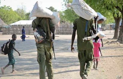 Rebel fighters walk through town after receiving food in Akobo, near the Ethiopian border, in South Sudan, Jan. 19, 2018.