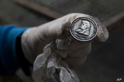 A worker holds a coin bearing the images of President Donald Trump and King Cyrus, to honor Trump's recognition of Jerusalem as Israel's capital, at a private minting facility, in Tel Aviv, Israel, Feb. 28, 2018.
