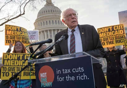 Sen. Bernie Sanders, I-Vt., joins protesters outside the Capitol as Republicans in the Senate work to pass their sweeping tax bill, a blend of generous tax cuts for businesses and more modest tax cuts for families and individuals, on Capitol Hill in ...