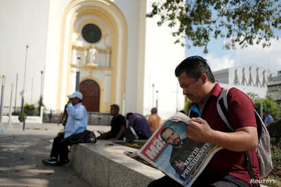 A man reads a newspaper with the picture of presidential candidate Nayib Bukele, who proclaimed himself the winner of the presidential election, in San Salvador, El Salvador, Feb. 4, 2019.