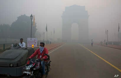 FILE - A man covers his face as he rides in front of the landmark India Gate, enveloped by smoke and smog, in New Delhi, India, Oct. 31, 2016. As Indians wake Monday to smoke-filled skies from a weekend of festival fireworks for the Hindu holiday of