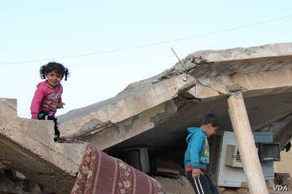 Children play on a bombed-out house in Tel Hamees, Syria, March 1, 2019. (H. Murdock/VOA)