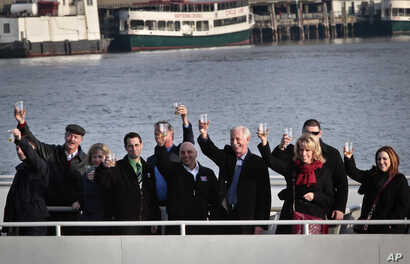 """FILE - Captain Chesley """"Sully"""" Sullenberger III, fourth from right, joins survivors and rescuers in a toast marking the anniversary of the event known as the """"miracle on the Hudson,"""" Jan. 15, 2014 in New York."""
