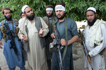 Afghan Taliban militants stand with residents as they took to the street to celebrate a cease fire on the outskirts of Jalalabad on June 16,2018.